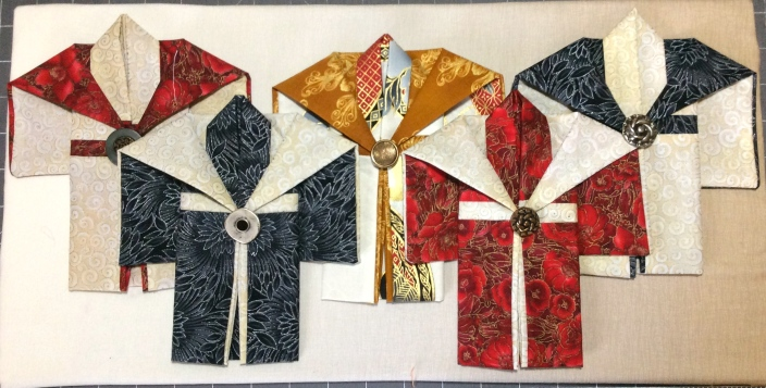 Mounting on the shadowbox background with small pins at top and bottom of each kimono