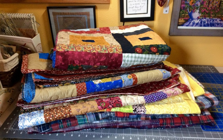 """Please complete us"" (Pile-o-Quilts waiting for their bindings to be sewn down)"